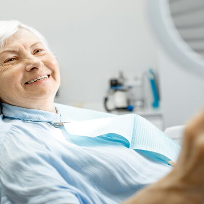 older woman at dentist smiling at her new smile
